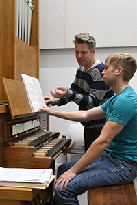 professor and student in organ lesson