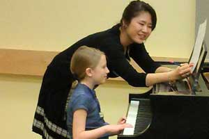 UI piano student works with girl in Pre-College Piano Conservatory program.