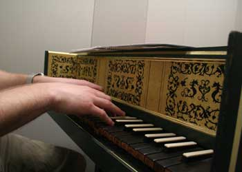 Fingers playing a harpsichord