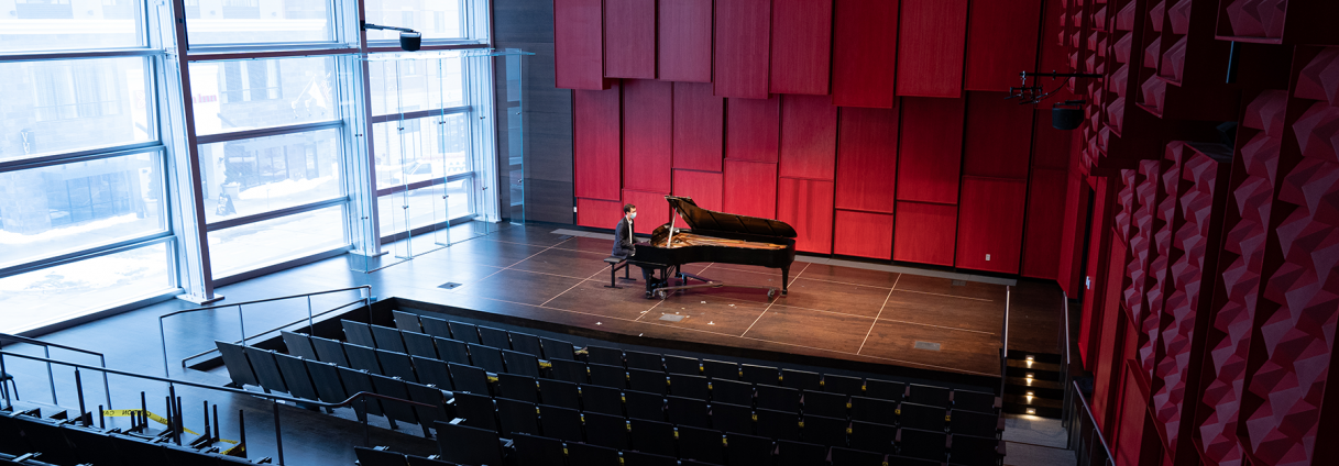 Solo student pianist in empty Recital Hall