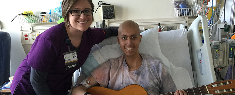 Music therapy student Emily Guthe works with a patient in the hospital.