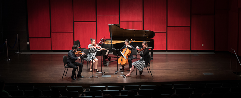 A string quartet performs in the recital hall.