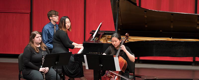 Student piano trio performing in recital hall