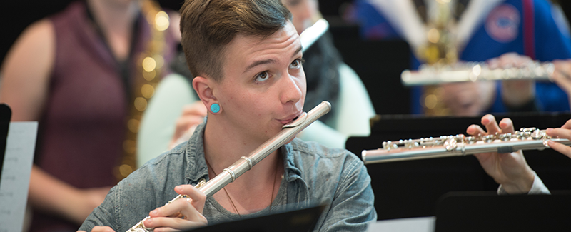 male flute player in band rehearsal