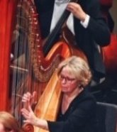 Photo of Pam Weest-Carrasco seated at a harp during an orchestra concert