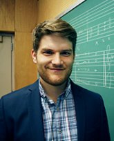 Photo of Robert Komaniecki standing next to a chalkboard with music theory diagrams