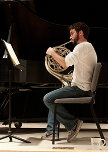 Horn player rehearses on stage.